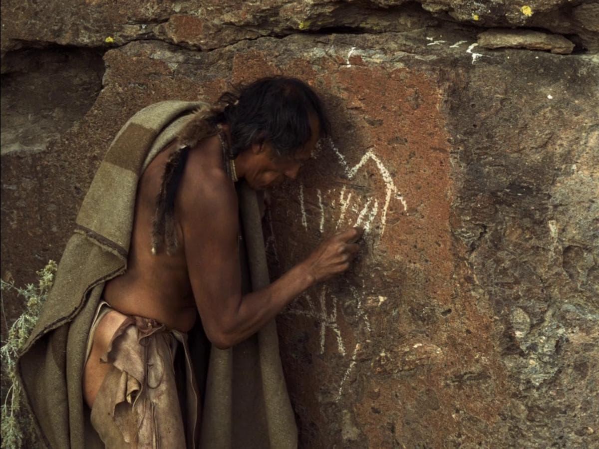 L'indien dessine des inscriptions sur le mur dans La Dernière Piste