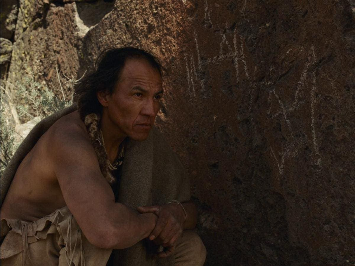 L'indien devant des inscriptions dans La Dernière Piste