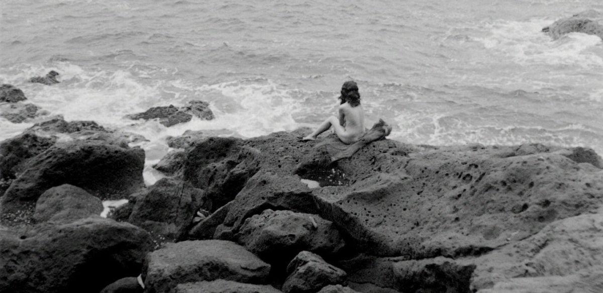 Akemi Negishi sur les rochers devant la mer dans Fièvre sur Anatahan