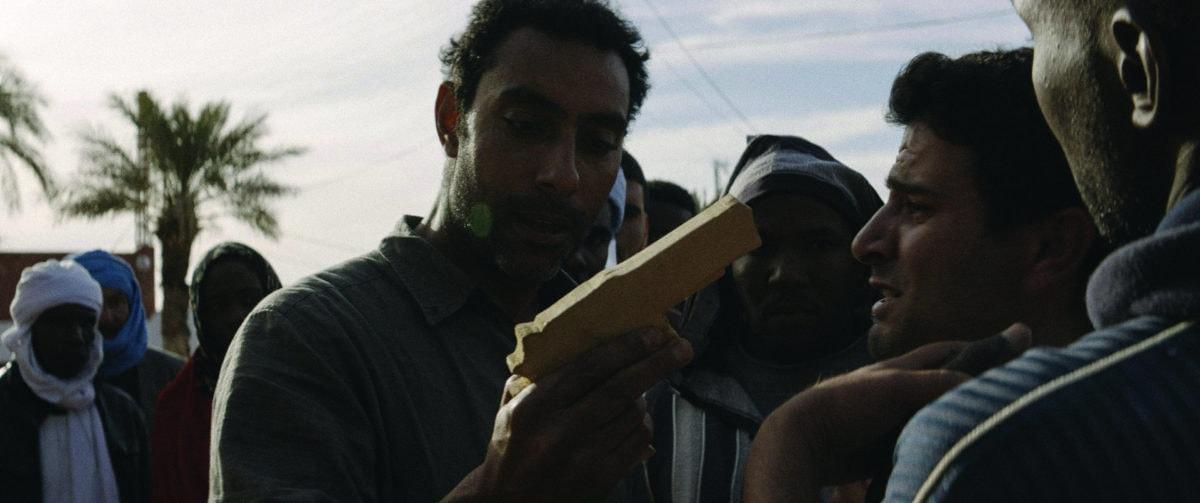 Slimane Benouari fusil à la main dans Abou Leila