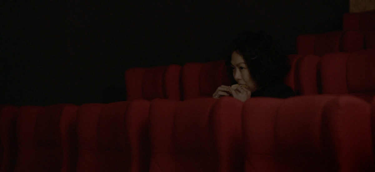 Kim Min-hee assise dans une salle de cinéma dans La Femme qui s'est enfuie
