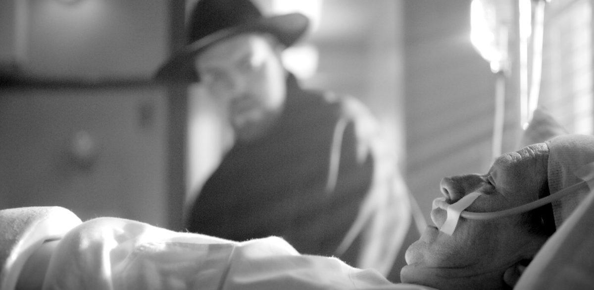 Mank (Gary Oldman) couché dans son lit devant Orson Welles (Tom Burke) dans Mank