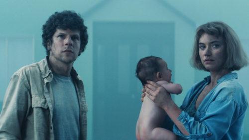 Gemma (Imogen Poots) et Tom (Jesse Eisenberg) avec leur enfant devant leur maison dans Vivarium