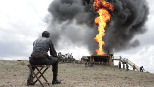 Daniel Plainview (Daniel Day-Lewis) assis devant un puit de pétrole en feu dans There Will Be Blood
