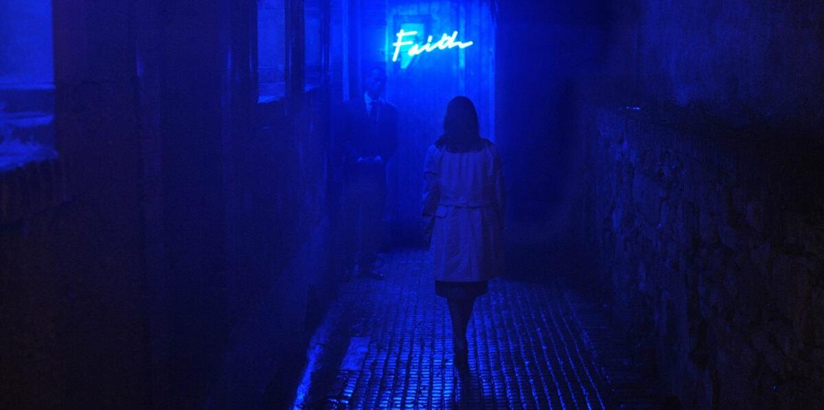 Gloria (Lola Dueñas) marche dans une rue éclairée en bleu dans Alleluia