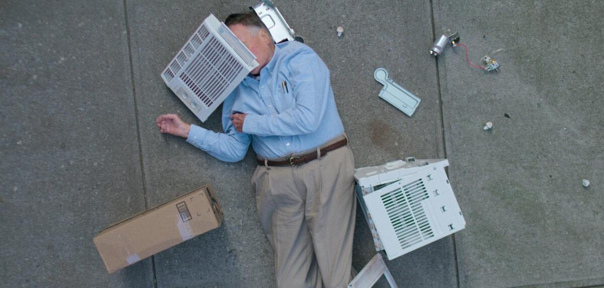 Dick Johnson, étalé sur un trottoir avec une caisse sur son visage, dans Dick Johnson is Dead
