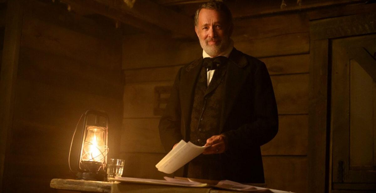 Tom (Tom Hanks) lit des journaux devant le peuple dans La Mission