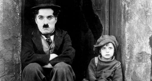 Charlie Chaplin et Jackie Coogan assis dans la rue dans Le Kid