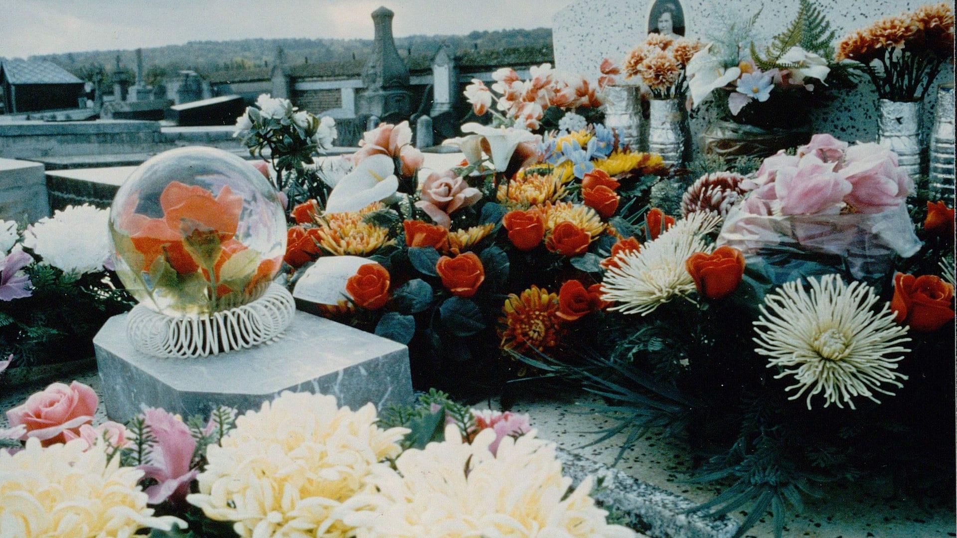 Une tombe recouverte de fleurs dans Des morts