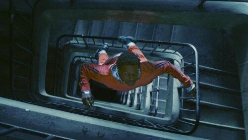 Youri (Alséni Bathily) vole à travers la cage d'escalier de son immeuble dans Gagarine