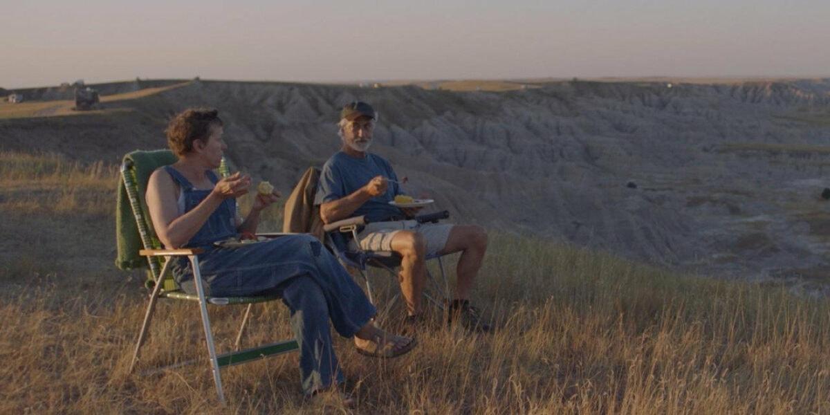 Fern (Frances McDormand) et Dave (David Strathairn) assis près de leur camping-car dans le désert dans Nomadland