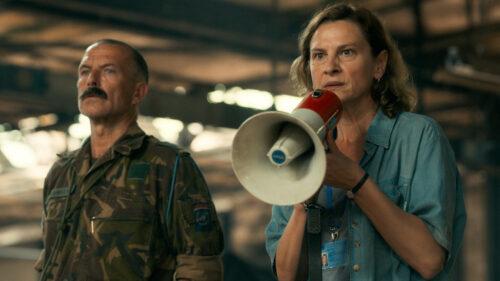 Aïda (Jasna Djuricic) parle au microphone devant la foule dans La voix d'Aïda