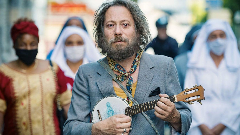 Tralala joue du banjo dans la rue dans Tralala